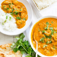 overhead shot of two servings of indian butter chicken in white bowls with white rice and cilantro garnish and pita bread on the side