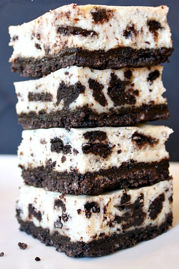 four pieces of cookies and cream cheesecake bars stacked on top of each other