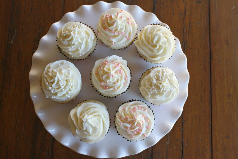 overhead shot of white frosted cupcakes on a white cake platter