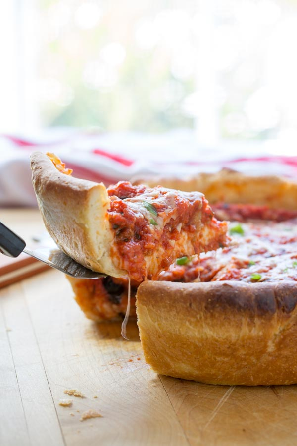 chicago style deep dish pizza pulling out a slice with a spatula