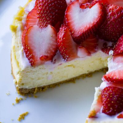 Instant Pot Cheesecake with piece cut out and strawberries on top on white plate