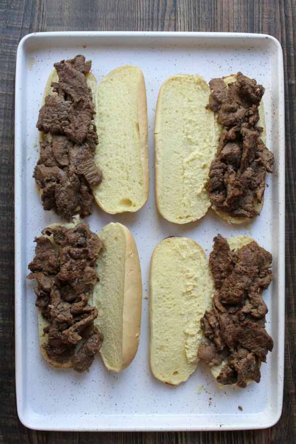 cajun cheesesteak sandwiches open faced on white baking sheet ready to add cheese and bake