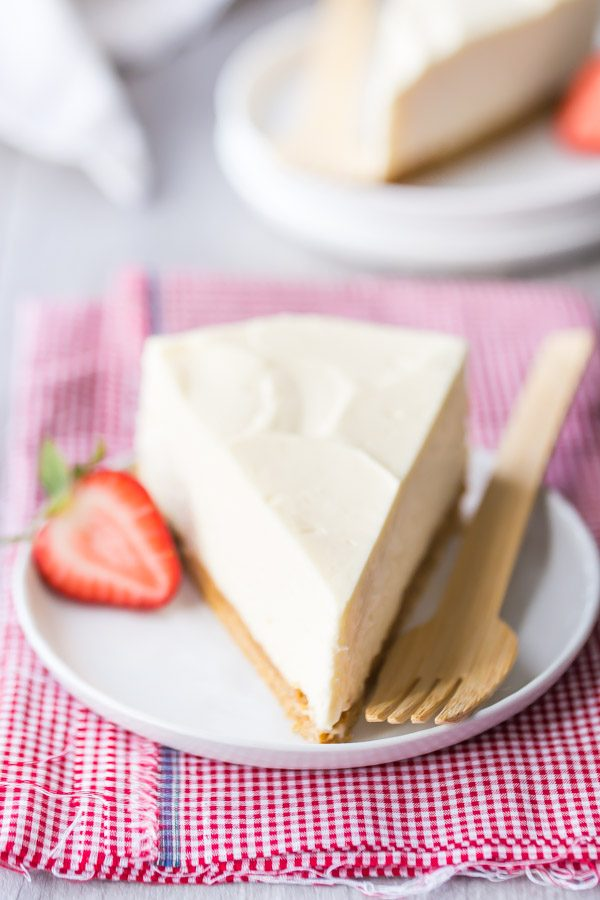 slice of no bake cheesecake on a white plate with fork and strawberry, sitting on a red/white checked napkin. peek at another slice of cheesecake in the background