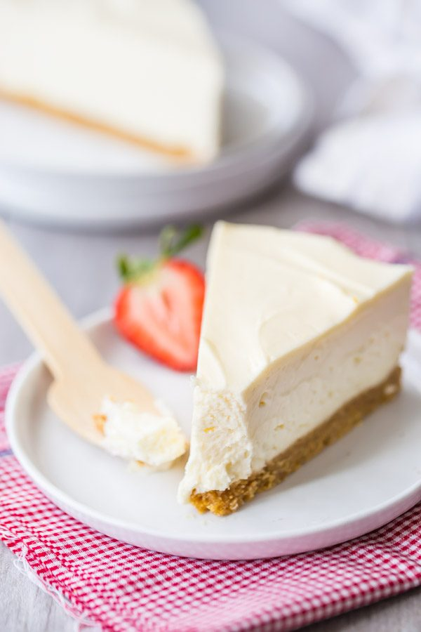 slice of no bake cheesecake with a bite out of it on a white plate with a wooden spoon and a strawberry. sitting on a white and pink checked napkin