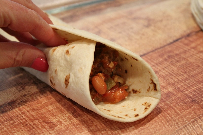 wrapping a tortilla around beef and bean filling