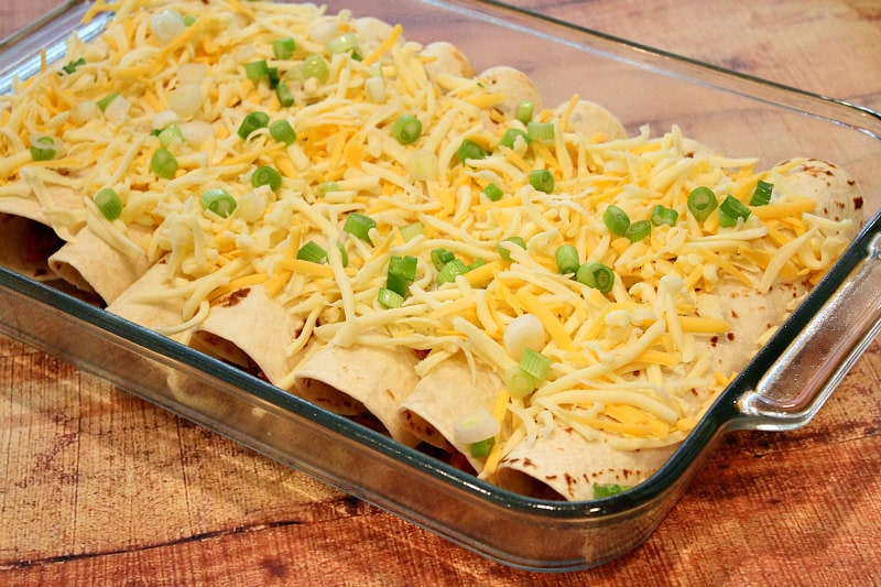 beef burrito casserole ready to go in the oven with shredded cheese and green onions on top