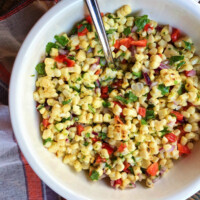 grilled corn salad in a white bowl with a serving spoon on top of an orange, purple and white striped cloth napkin