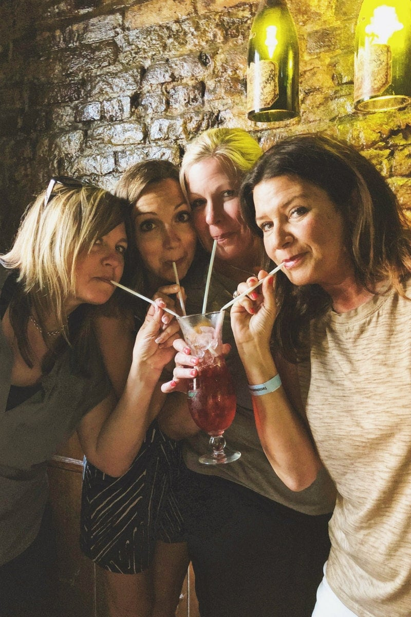 four girls sharing a hurricane cocktail with straws