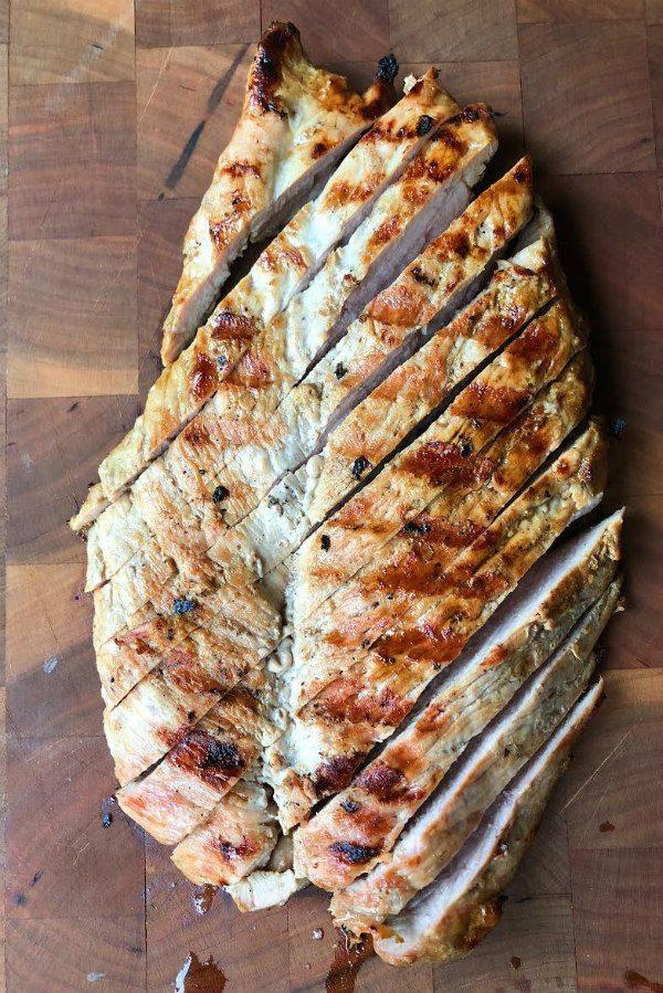 Grilled Pork Tenderloin sliced on a wooden cutting board