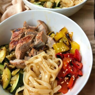 grilled pork and vegetable teriyaki noodle bowl in a white bowl. a peek at a 2nd noodle bowl in the background
