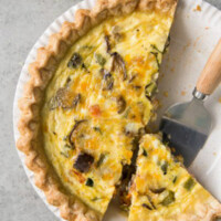 Summer Vegetable Quiche in a white pie plate with a couple of pieces cut out and a pie server on the plate