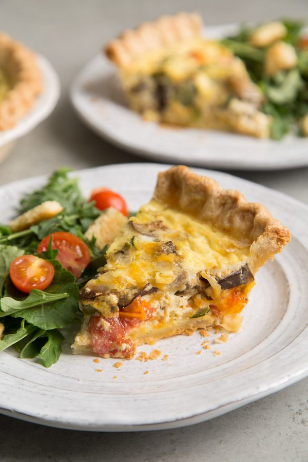 Slice of Summer Vegetable Quiche on a white plate with salad and more plated quiche in the background
