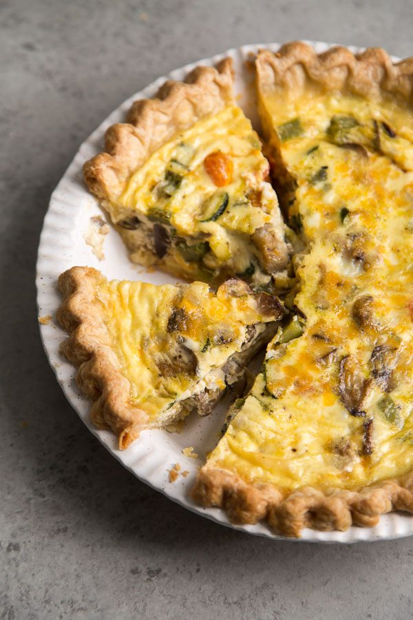 Summer Vegetable Quiche in a white pie plate with a couple of pieces cut out