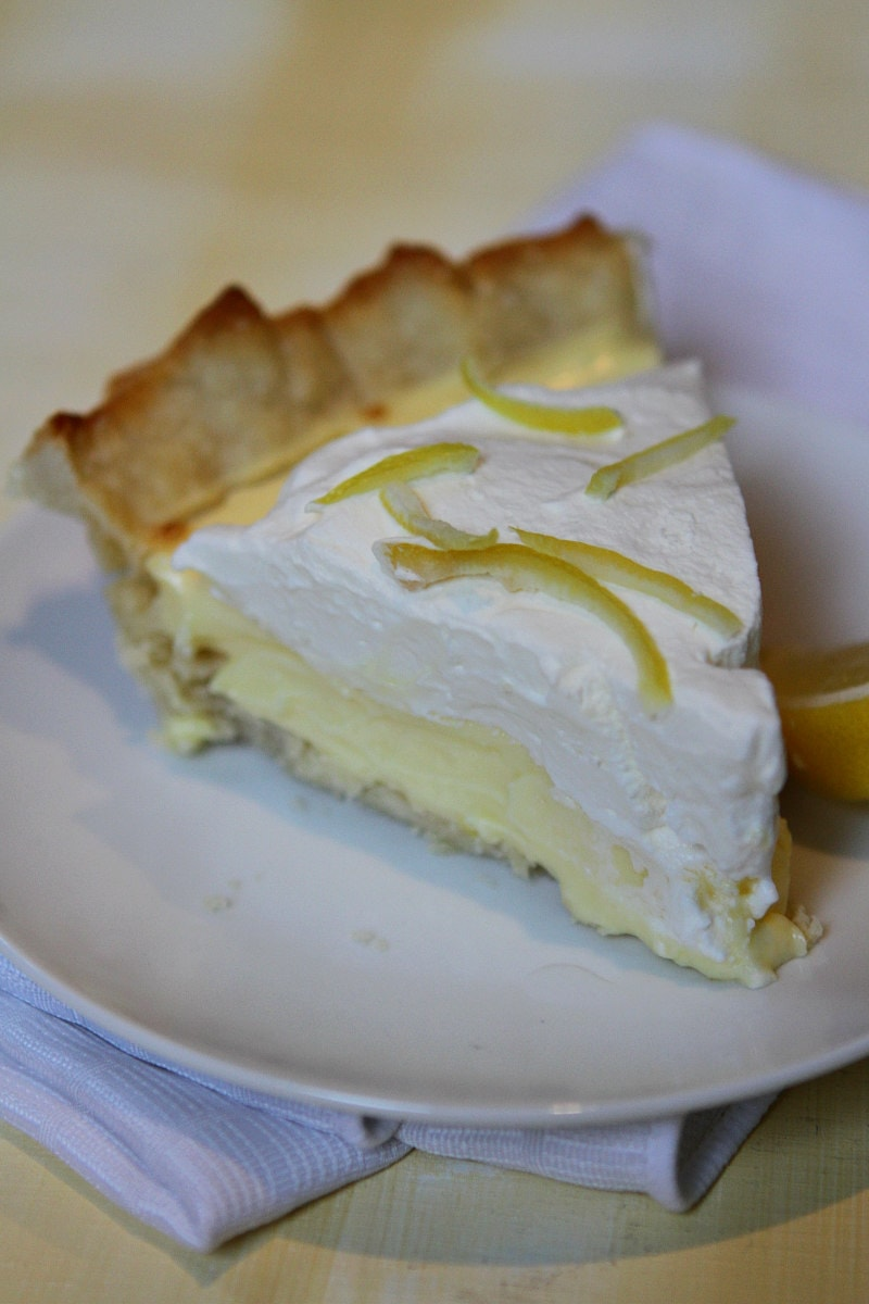 slice of Lemon Sour Cream Pie on a white plate set on a white napkin