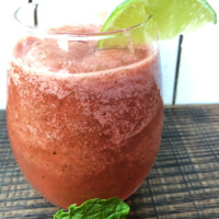 slushie watermelon mojitos in a glass garnished with a lime wedge and a mint leaf in front of the glass