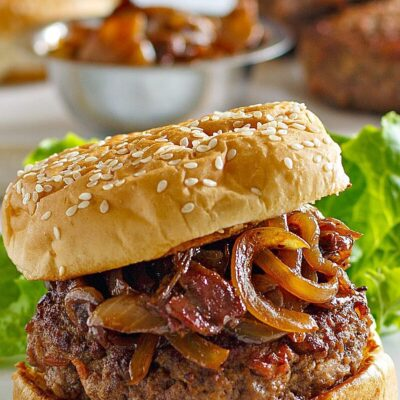 Bacon Burger with Balsamic Caramelized Onions on a white serving platter with lettuce leaf. More buns, burgers and bowl of caramelized onions in the background.
