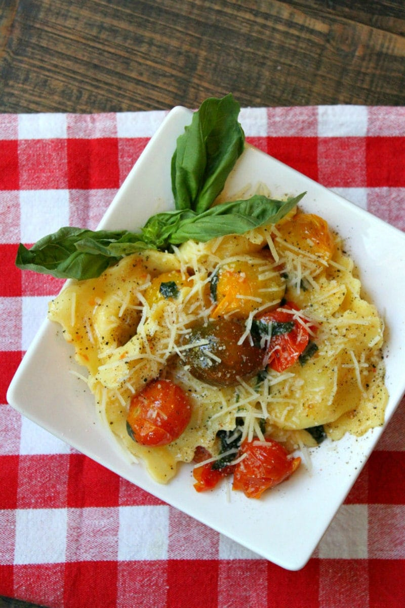 overhead shot of brown butter ravioli with tomatoes on a white plate set on a red/white checked napkin
