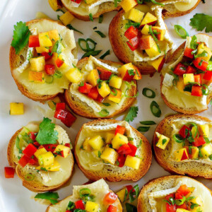 overhead shot of peach and brie bruschetta on a white serving platter