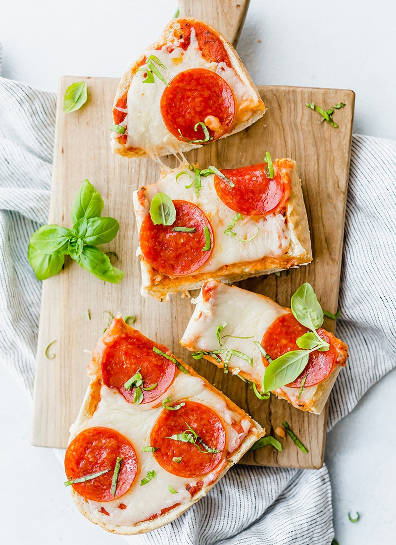 French Bread Pizza with Pepperoni and fresh basil cut into slices