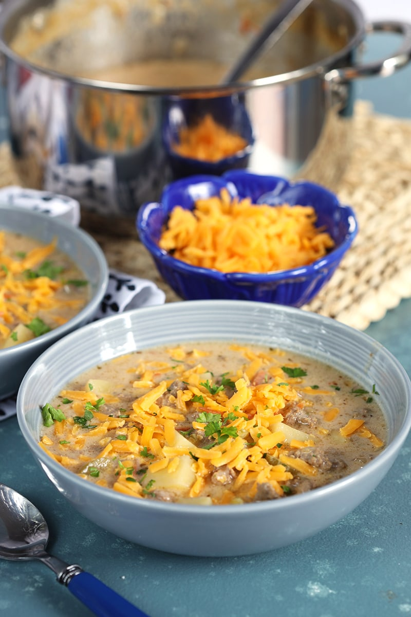 Creamy cheeseburger soup in a gray bowl with grated cheddar on top on a blue background.