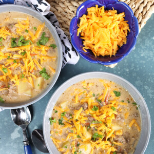 Overhead shot of two bowls of creamy cheeseburger soup with a bowl of grated cheddar cheese.
