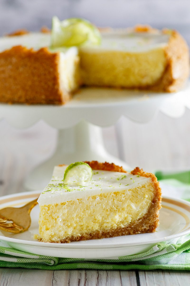 Slice of Key Lime Cheesecake on a white plate with a fork, set on a white and green napkin with cut cheesecake on display platter in the background