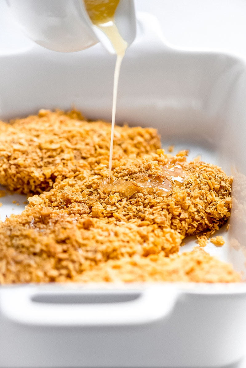 Making Baked Cornflake Chicken- chicken dipped and placed in white casserole dish with melted butter being poured on top