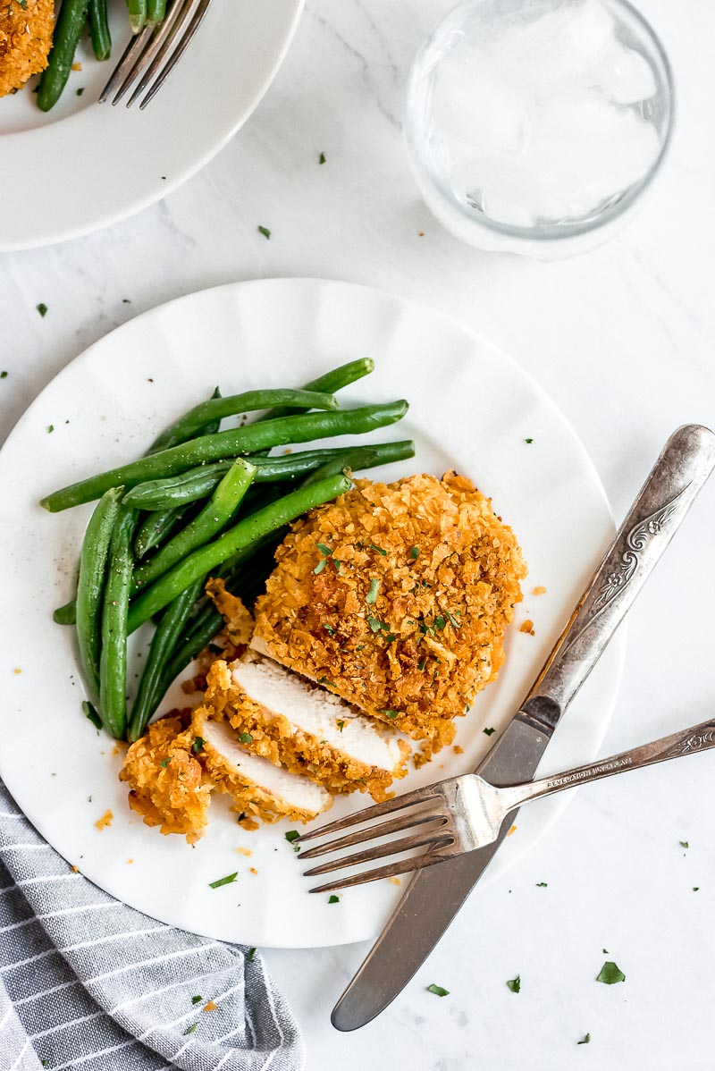 Baked Cornflake Chicken cut into slices on a white plate with green beans and a knife and fork.