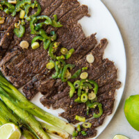 sliced carne asada on a white serving platter topped with jalapeno and with green onions and limes on the side
