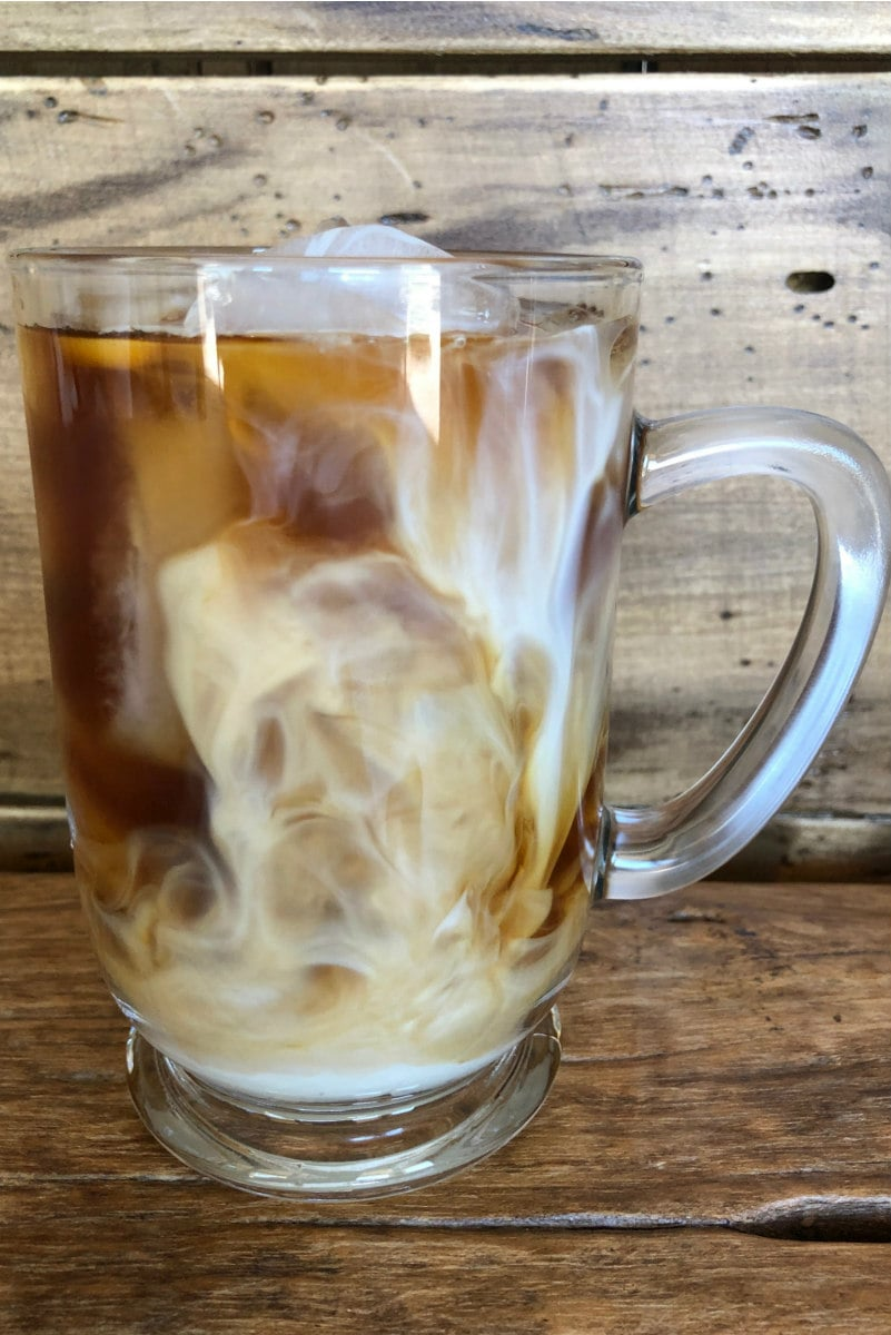 glass mug of cold brew coffee with cream swirling around in it