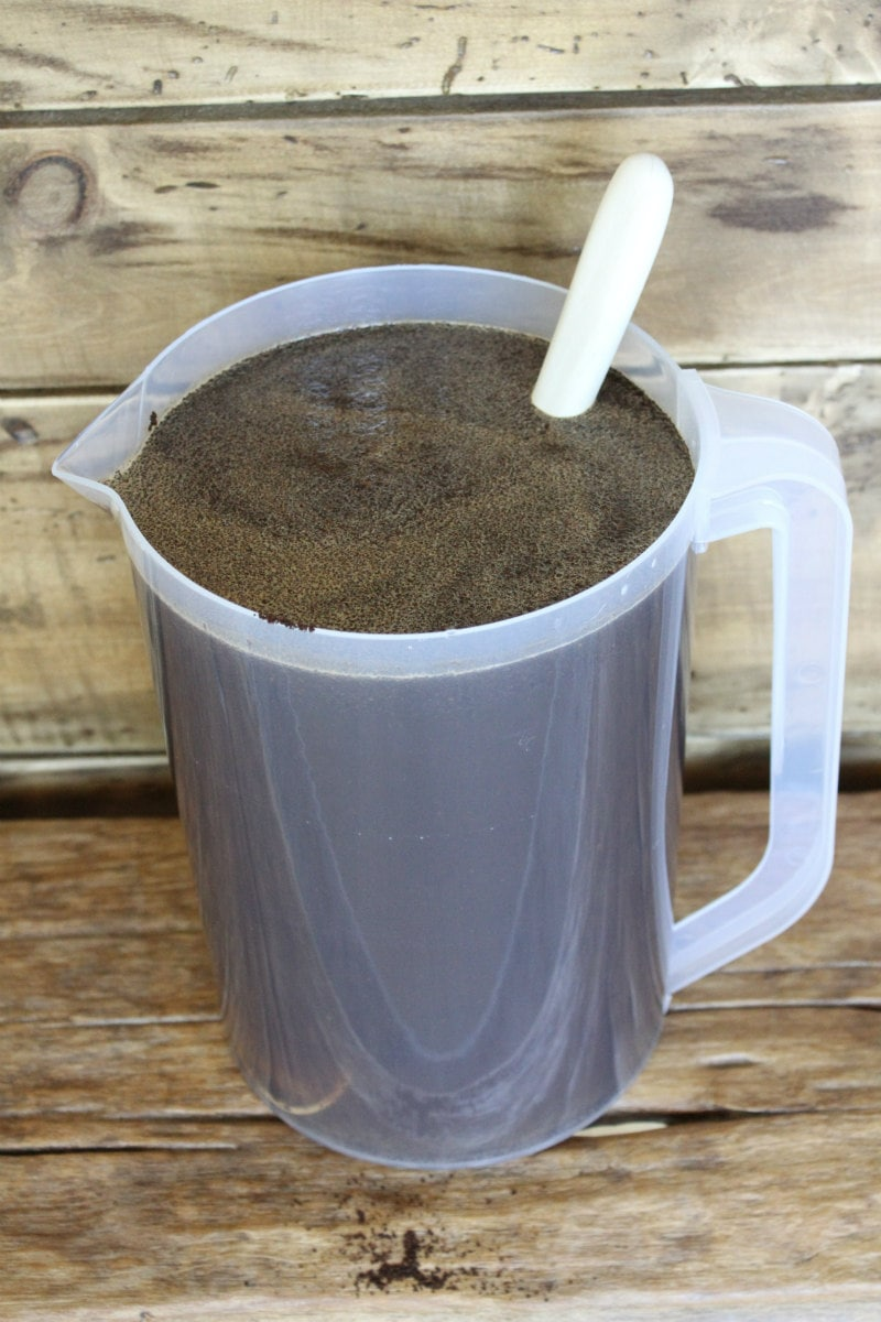 pitcher of cold brew coffee with coffee grounds marinating in the pitcher