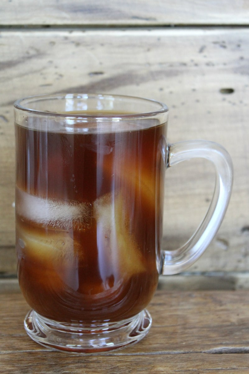 glass mug of cold brew coffee with a wooden backdrop