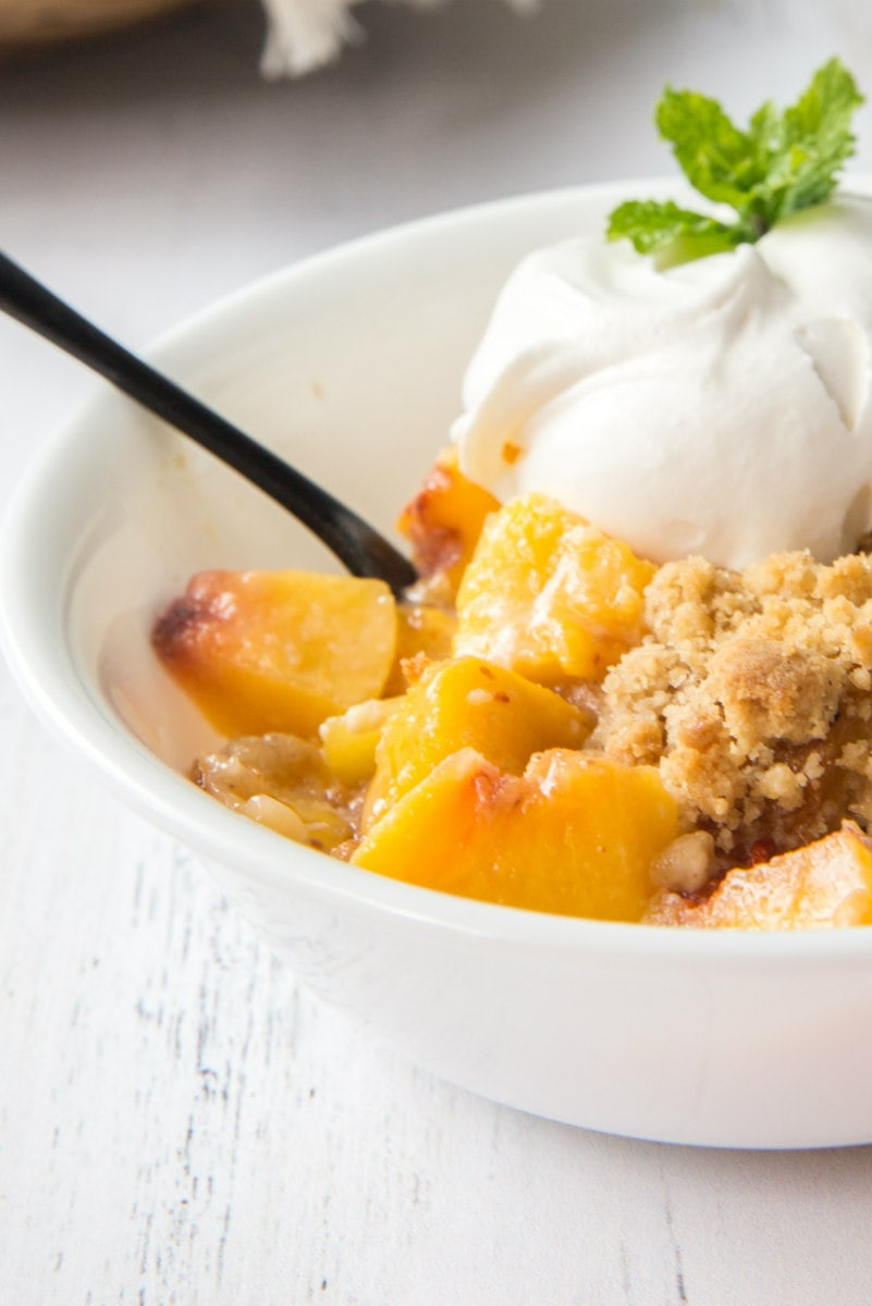 close up of a serving of peach cobbler french toast casserole in a white dish, garnished with whipped cream and fresh mint. Spoon in the bowl