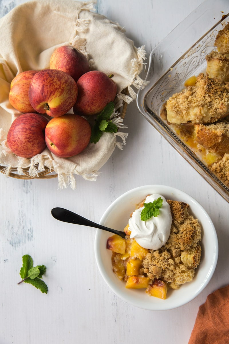 serving of peach cobbler french toast casserole in a white bowl garnished with whipped cream and fresh mint with basket of fresh peaches in the background