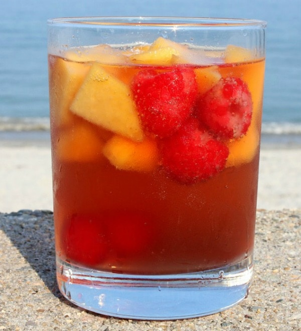 glass of carolina peach sangria sitting on a sea wall with the beach in the background