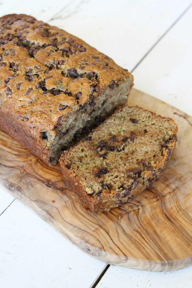 loaf of chocolate chip zucchini bread on a cutting board and slice cut off