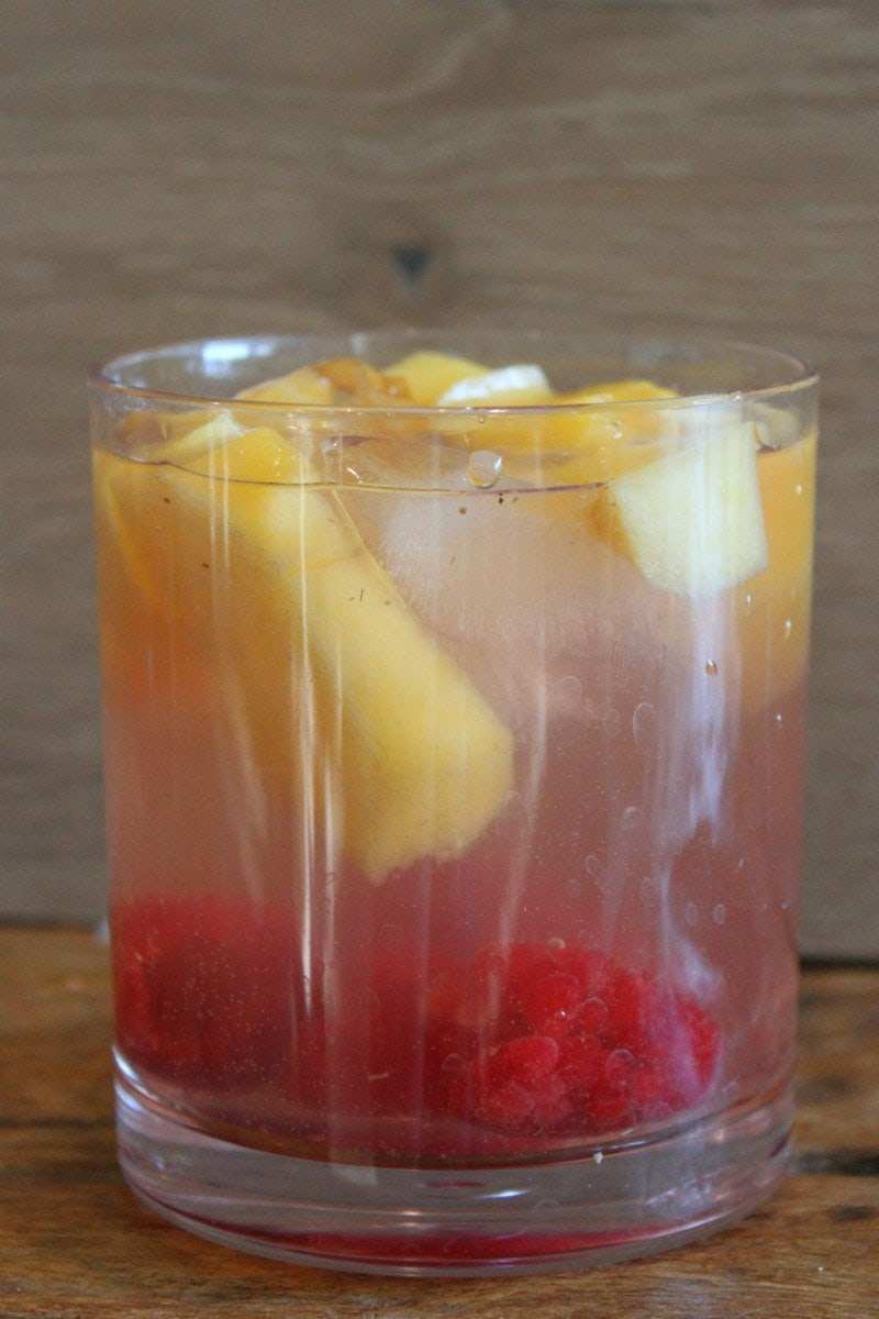 peach and raspberry sangria in a glass with a wood backdrop