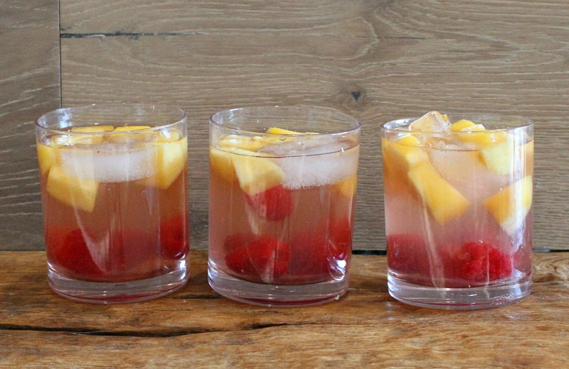 three glasses of peach and raspberry sangria with a wooden backdrop