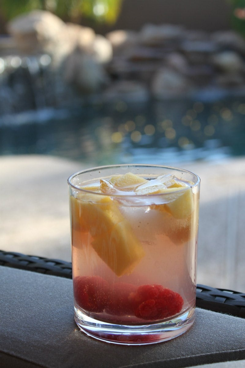 peach and raspberry sangria in a glass with a backyard backdrop