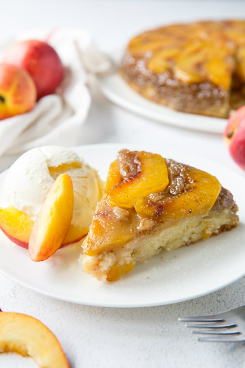 slice of peach upside down cake on a white plate with peaches and the cake in the background