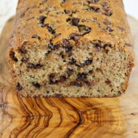 Loaf of chocolate chip zucchini bread cut open on a wooden cutting board