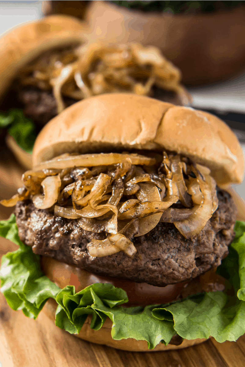 jucy lucy burger with grilled onions piled high