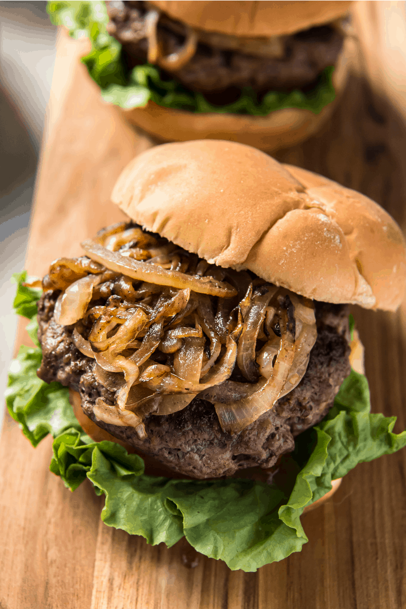 jucy lucy burger with lettuce and tomato and grilled onions piled high