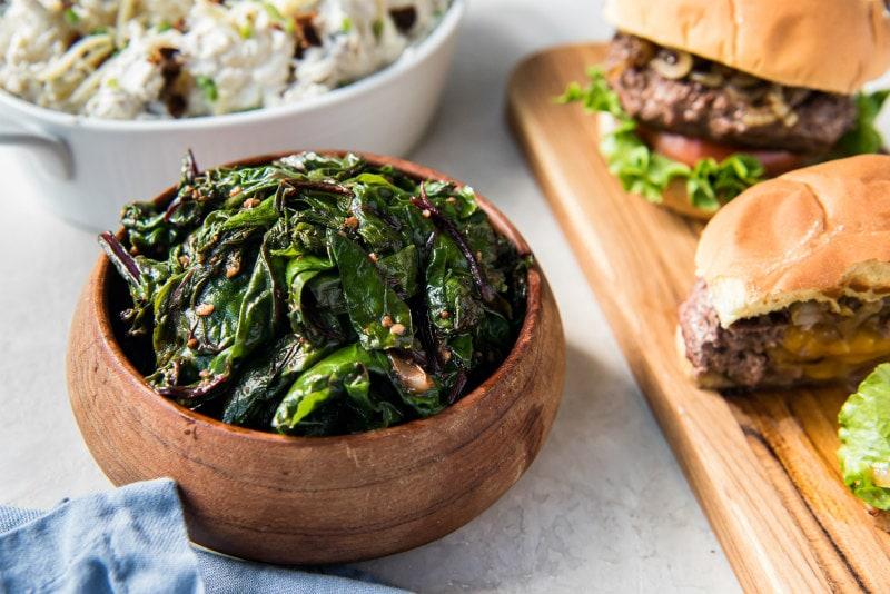 bowl of greens served alongside burgers