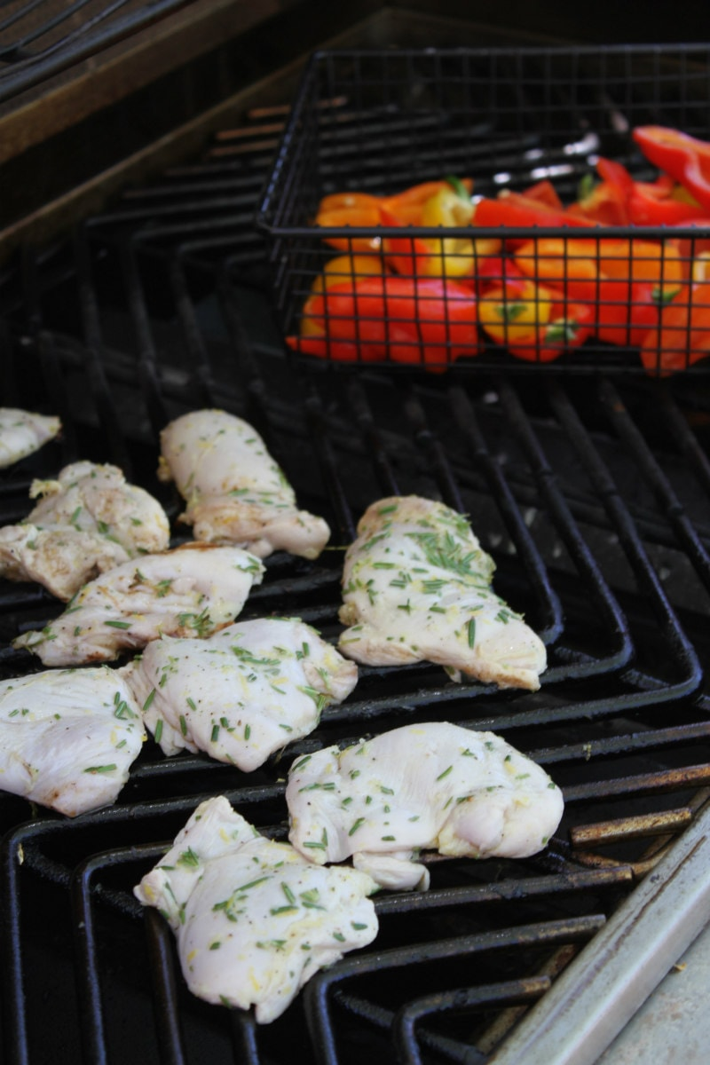 lemon rosemary grilled chicken thighs on the grill with peppers in a grill basket