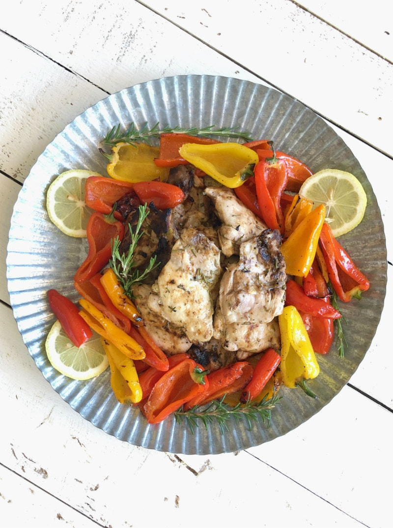 lemon oregano grilled chicken thighs in the center of a metal platter surrounded by grilled peppers and lemon slices