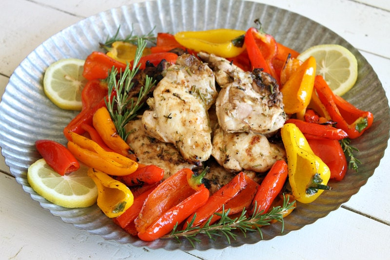 lemon oregano grilled chicken thighs in the center of a metal platter surrounded by grilled peppers