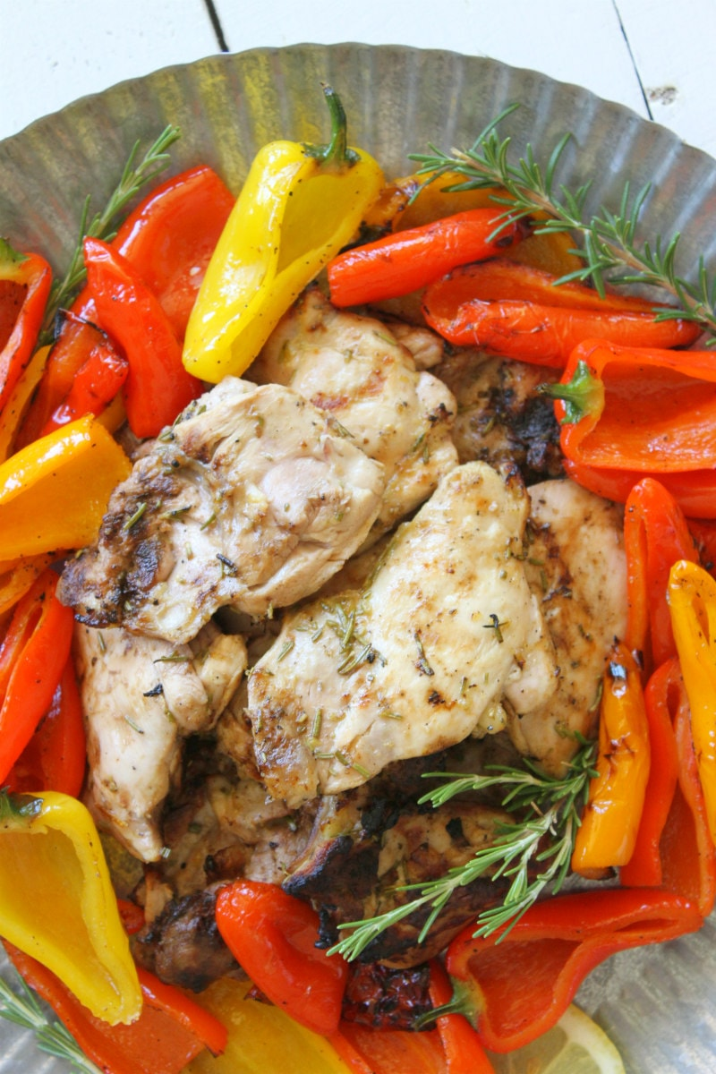 lemon rosemary grilled chicken thighs in the center of a metal platter surrounded by grilled peppers