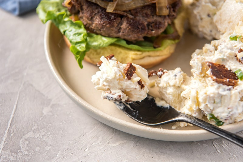 a forkful of potato salad on a white plate served with a burger