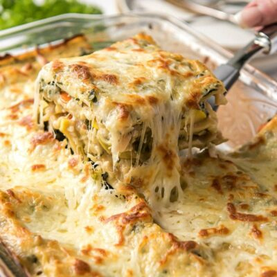 Pulling out a cheesy slice of vegetable lasagna out of the lasagna pan